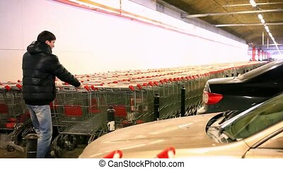 Man with shopping cart on parking of carts HD 1920x1080 -...