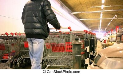 Man with shopping cart on parking of carts - Man with...