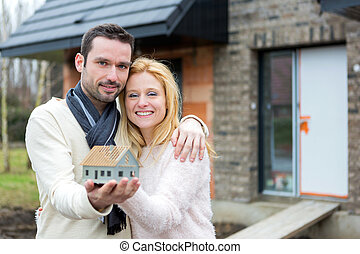 Young happy couple handling a miniature house - VIew of a...