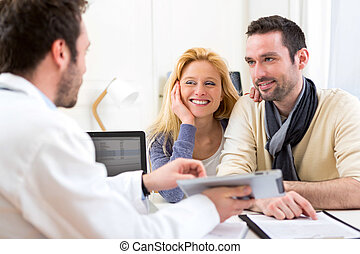 Young attractive couple seeing a doctor - View of a Young...