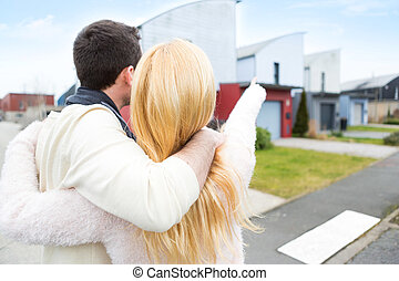 Young happy couple in front of their new house
