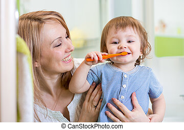 mother and little son brushing teeth in bathroom - smiling...