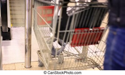 People go to the supermarket with shopping carts Close up -...