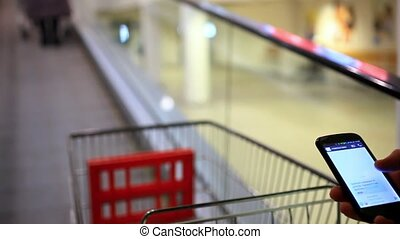 Businessmans hands using phone, send messages in the shopping mall until go escalator with trolley. Close up.