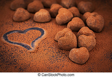 Heart shaped chocolate truffles on cocoa powdered table,...