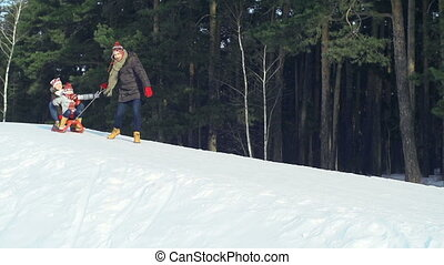 Gonna Catch You - Slow motion of father pulling sled with...