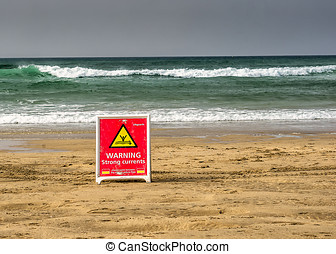 warning strong currents sign - warning sign standing on the...