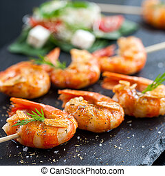 Shrimp tails grilled on wood skewer. - Macro close up of...