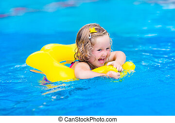 Little girl in swimming pool - Cute funny little toddler...