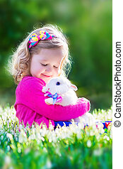 Little girl playing with a rabbit - Adorable little girl,...