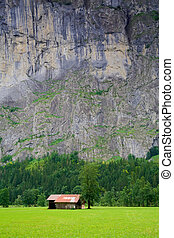 Small Barn close to a Steep Rocky Mountain in Switzerland -...