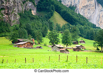 Houses and barns are close to a steep rocky mountain near...