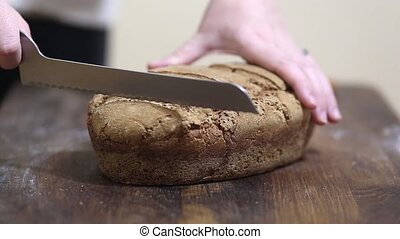 Baker cutting fresh bread - Baker is cutting freshly baked...