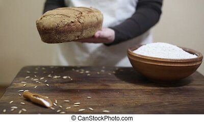 Baker putting bread on wooden table - Baker is gently...