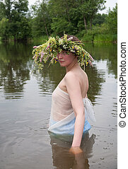 Girl in river - Girl dressed in pareo and flower wreath in...
