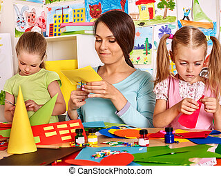 Child cutting out scissors paper. - Children with teacher...