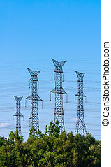 Four electrical towers on sky behind trees - Four large...