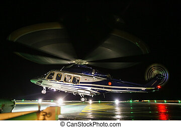 Helicopter landing on oil and gas platform in night time for...
