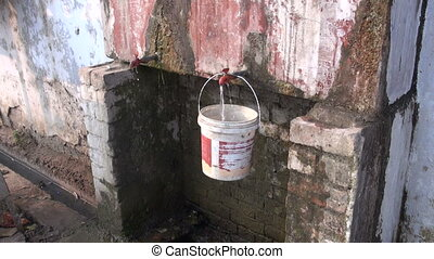 old and dirty drink water tap with plastic bucket in Agra...
