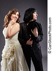 Elegant lesbian couple posing as bride and groom, on gray...