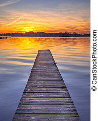 Majestic Sunset over Wooden Jetty in Groningen, Netherlands...
