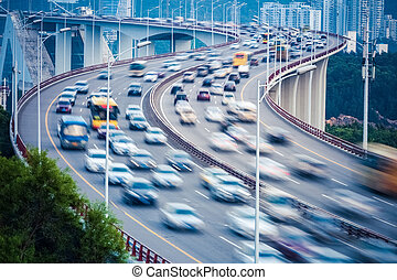 curved ramp bridge with busy traffic vehicles motion blur