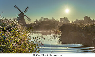 Dutch windmill in hazy wetland - Characteristic historic...