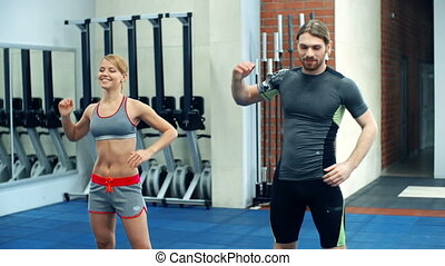 Keeping Fit - Woman and man performing physical drill...