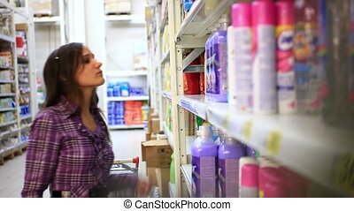 Beautiful young woman shopping in the store household chemicals and cosmetics. Selects fabric softener. HD. 1920x1080