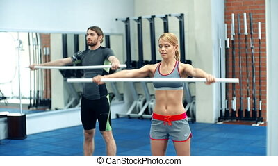 Crossfit Workout - Two sportsmen training in gym with a bar