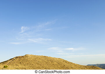 Hill - arid hill with blue sky