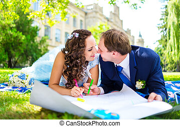 Happy man and woman colouring or drawing hearts at the garden. Love concept