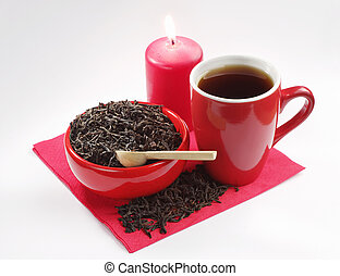 Red ceramic dishes with black tea and a burning candle