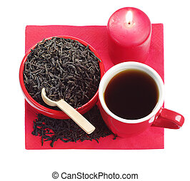 Red dishes with black tea and a burning candle isolated on...