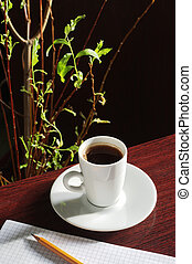 Cup coffee and notepad on a wooden table in sunlight
