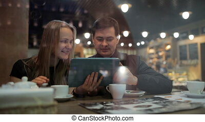 Sharing their online photo album at the cafe - Shot of a...