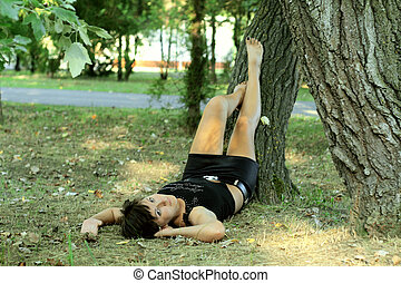 Girl lays near the tree in park