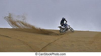 Motorcross dirtbike spraying sand - Man riding dirt bike in...