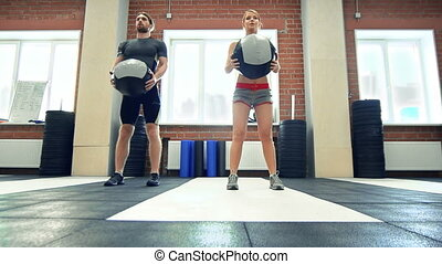 Ball Squat - Static shot of two squatting with a ball in a...