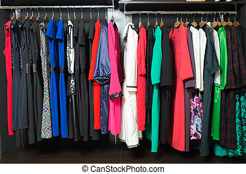 women's dresses on hangers in a retail shop - Colorful...