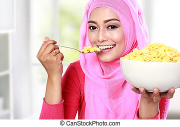 young muslim woman eating cereal - portrait of young muslim...
