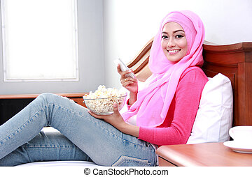 young muslim woman holding mobilephone and a bowl of popcorn