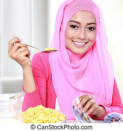 young muslim woman eating a cereal while reading a magazine...