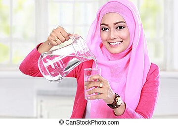 young muslim woman pouring water into a glass - portrait of...