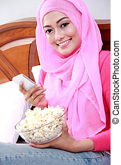 young woman wearing hijab holding a mobilephone and a bowl of po