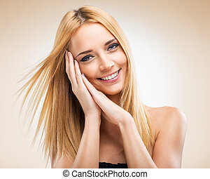 Beautiful blonde woman with hands in the face of - light background