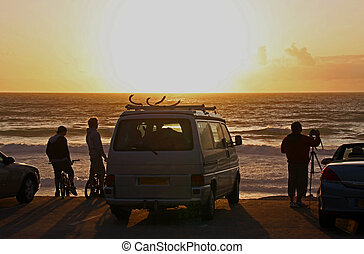 People at the coast watching an ocean sunset - People at the...