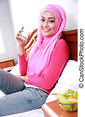 young muslim woman holding a glass of milk for breakfast -...