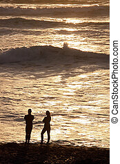 A couple on the beach at sunset - A couple talking at sunset...