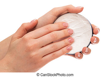 Woman applying moisturizer cream on hands with french...